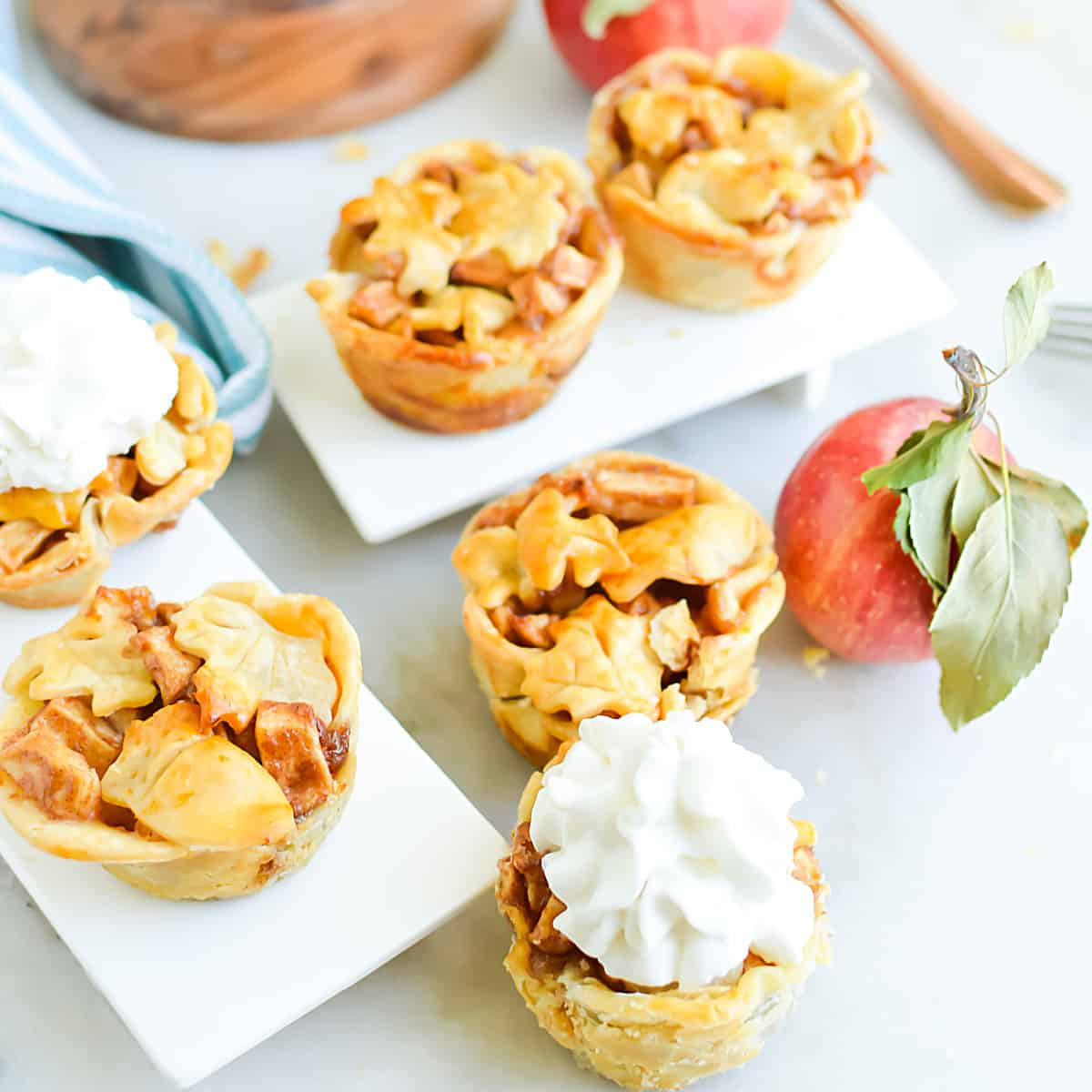 Square, close up image of mini apple pie tarts topped with whipped cream on a variety of white serving dishes.