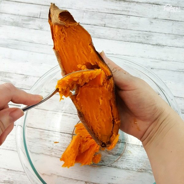 Hands removing the sweet potato skin.