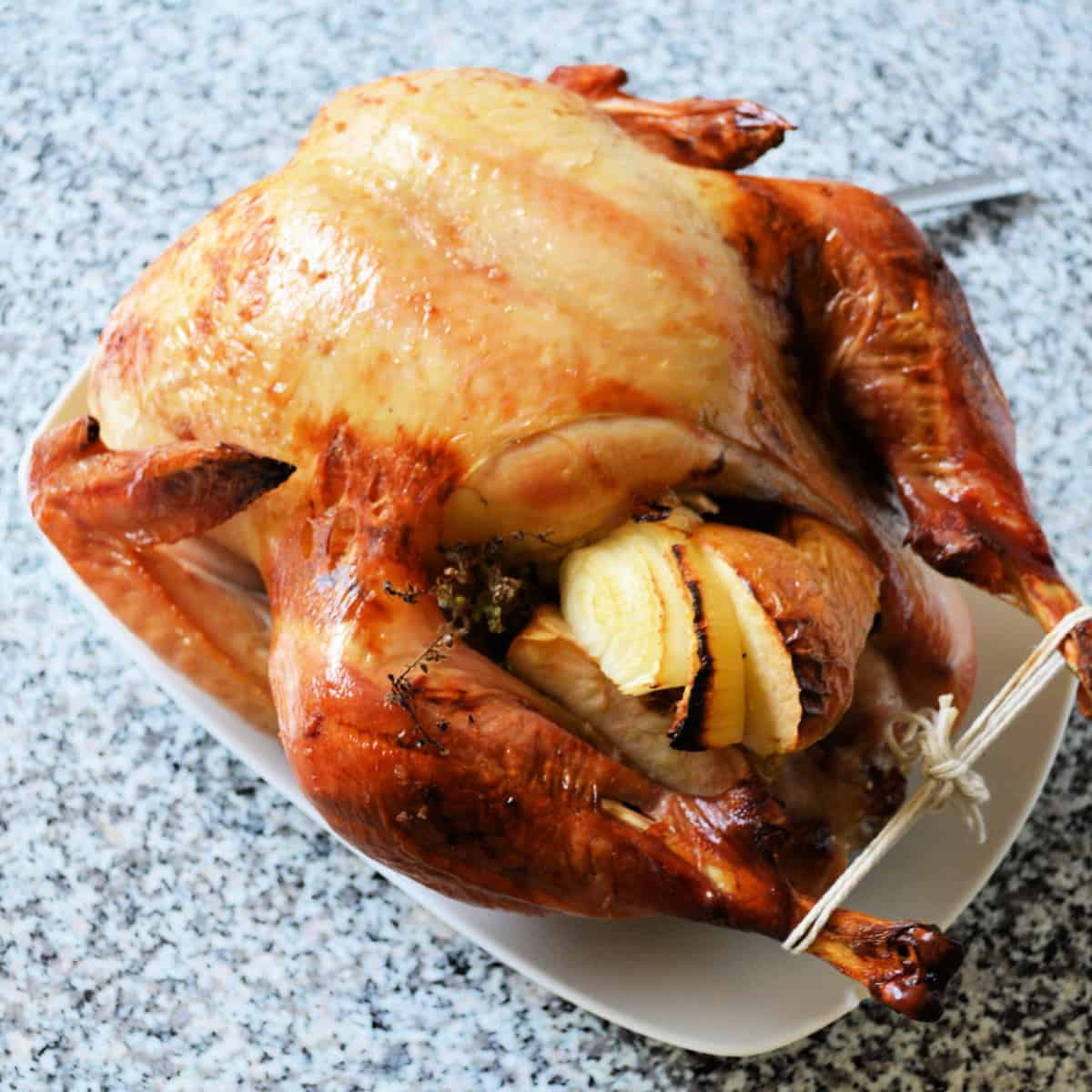 Roasted turkey stuffed with fruit and vegetables in a white serving dish.
