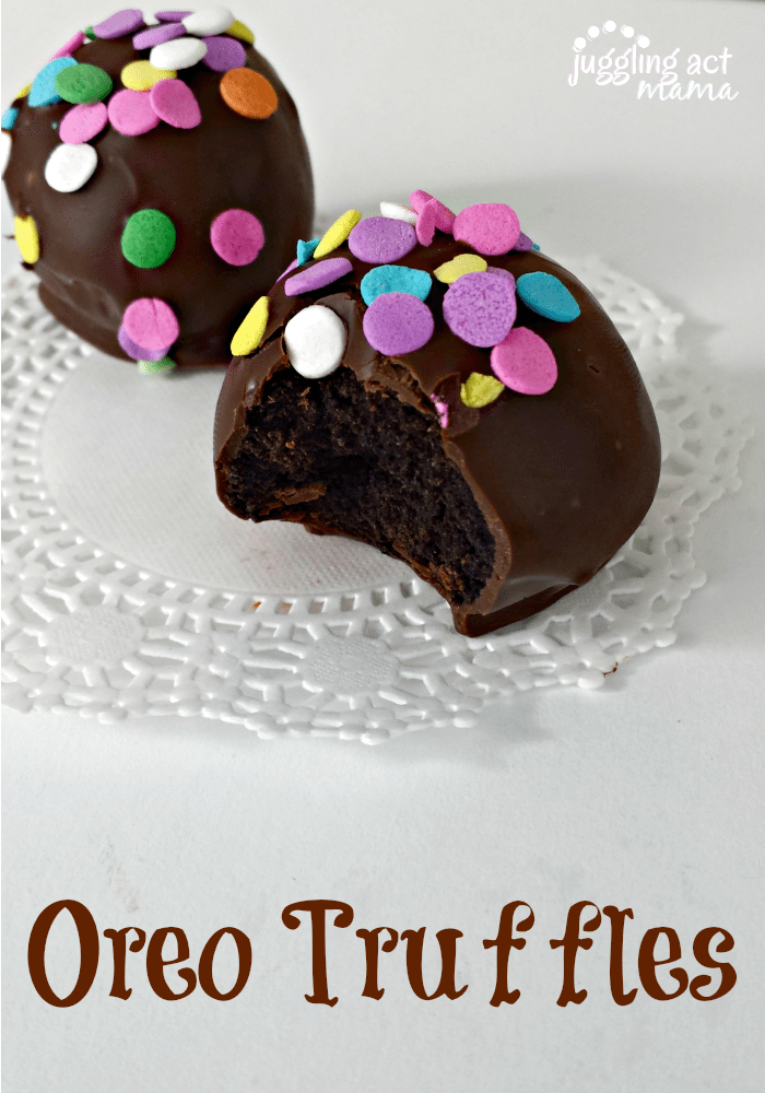 Two Oreo Truffles Balls, one with a bite taken out, decorated with colorful sprinkles.
