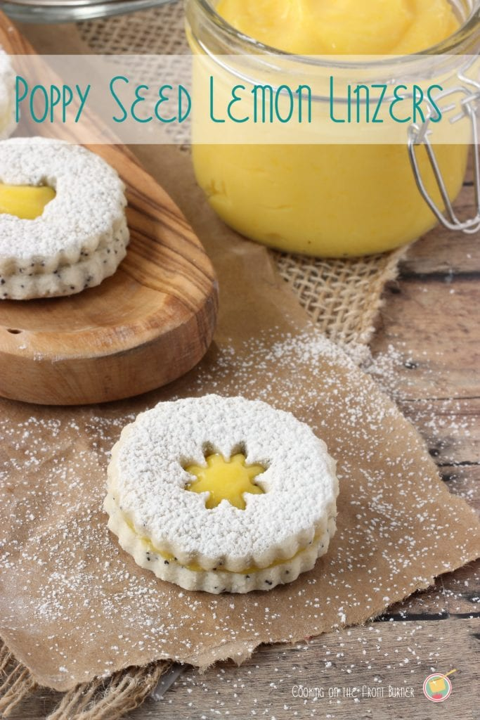 Two lemon poppy seed linzer cookies sit on top of a brown background. Each is sprinkled with powdered sugar. In the background, there is a clear jar filled with lemon curd.