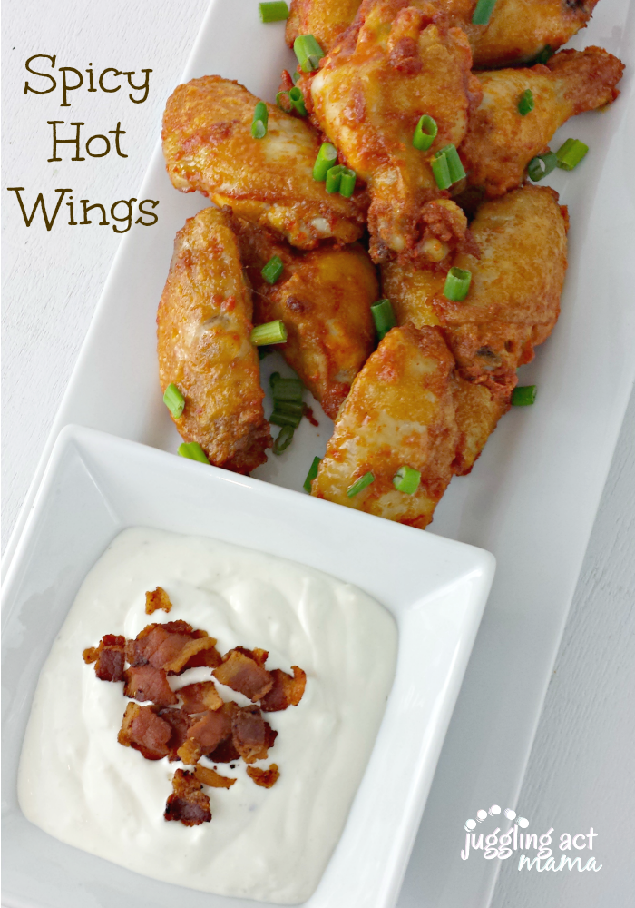 Spicy Wing Recipe - a tray of wings garnished with chives on a platter with blue cheese dressing.