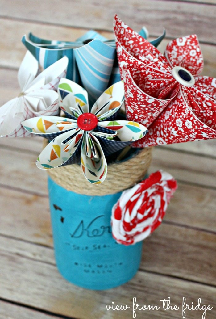 Red, white and blue paper flowers made with patterned paper in a blue mason jar with jute cording around the top and a white and red rolled fabric rose.