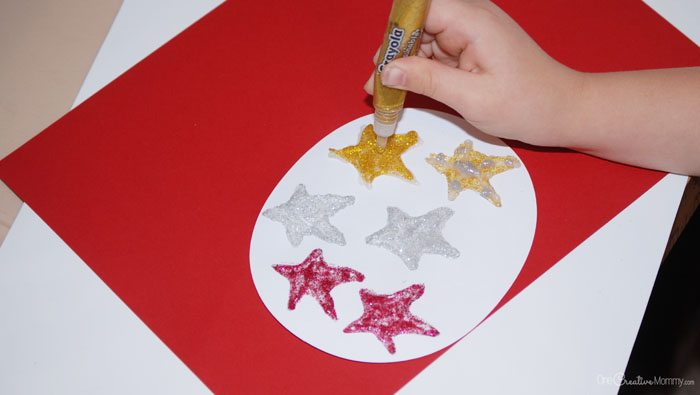 Creating the stars to top yarn Christmas trees. {Kids craft from OneCreativeMommy.com}