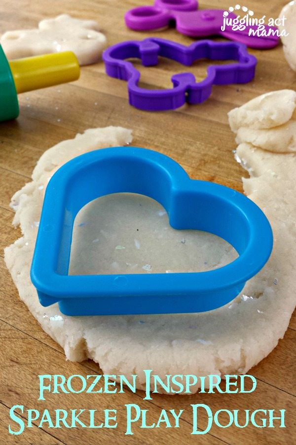 white parkle dlaydough with toy cookie cuttters on a cutting board.