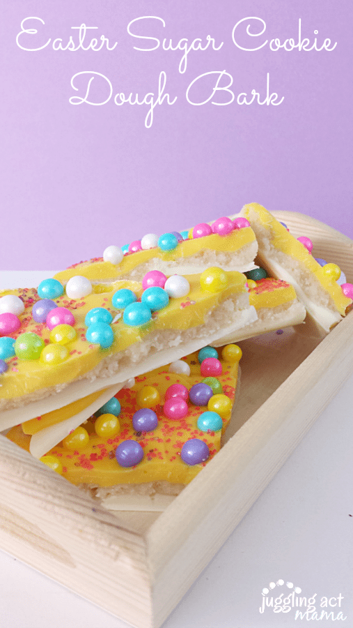 Easter Treats - an eggless Cookie Dough is sandwiched between two layers of chocolate and decorated with bright sixlet candies and festive sprinkles. The Easter treats are shown in a wooden container against a lilac background.