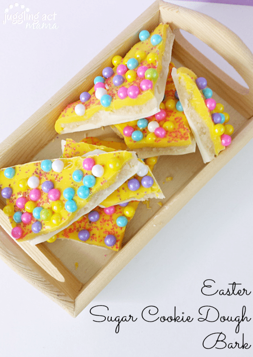 Easter Treats - an eggless Cookie Dough is sandwiched between two layers of chocolate and decorated with bright sixlet candies and festive sprinkles. The Easter treats are shown in a wooden container.
