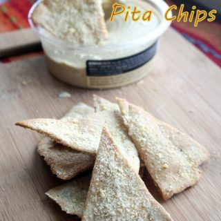 Photo of pita chips stacked high with a few in the back being dipped into hummus