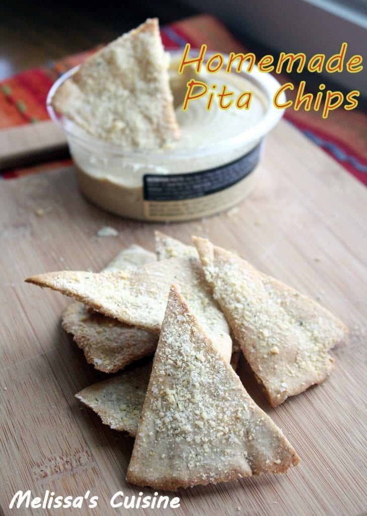 Pita chips sprinkled with parmesan cheese stacked in a pile on a wood cutting board with a container of hummus in the back with a pita chip dipped into it.