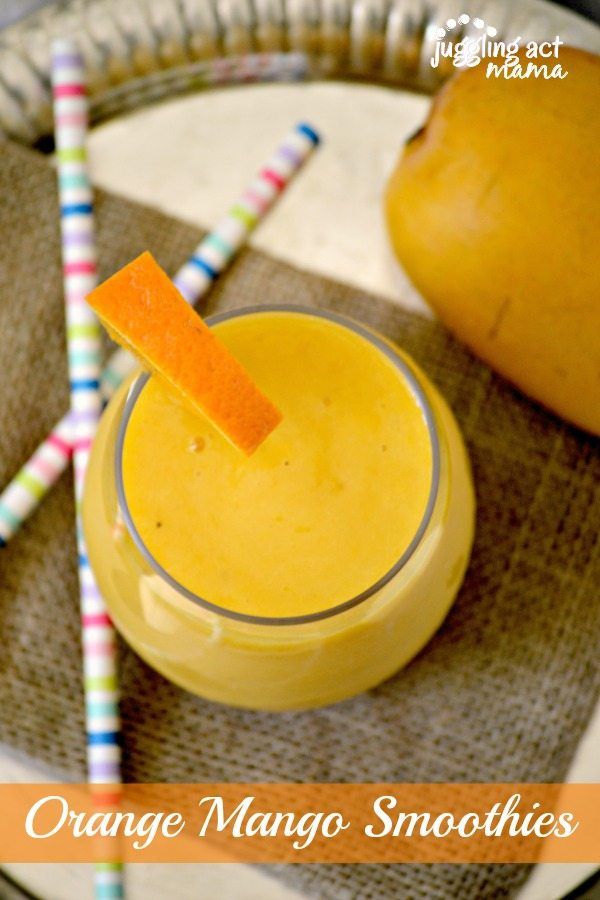 Top down view of an orange smoothie with mango in a clear glass.