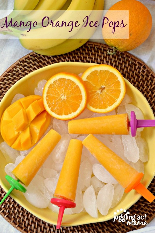Mango Orange Ice Pops shown on top of ice in a bowl next to fresh orange slices an cubbd mango
