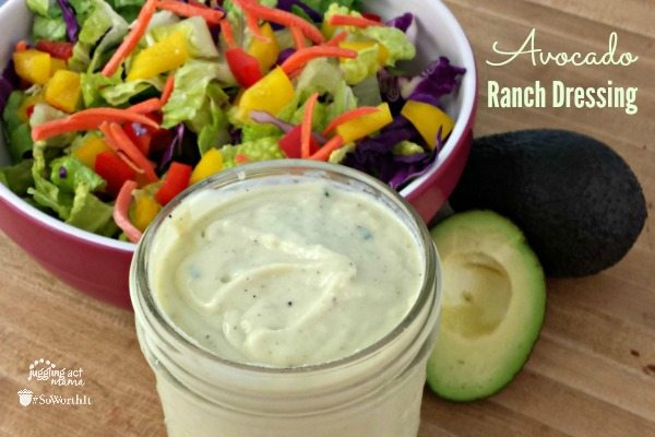 Avacado Ranch Dressing in a jar next to a bowl of salad