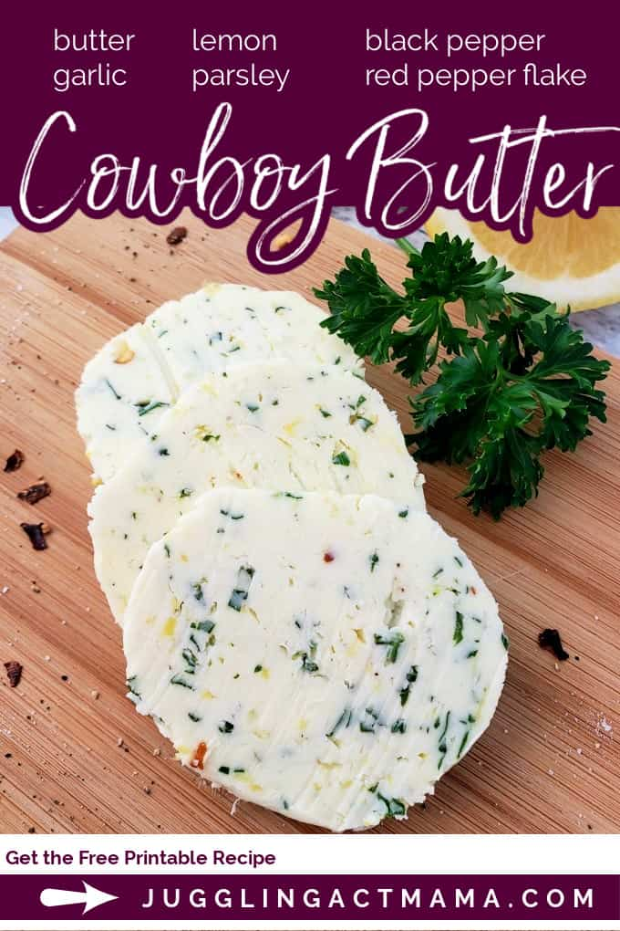 Slices of cowboy butter on a wood cutting board and surrounded by herbs.