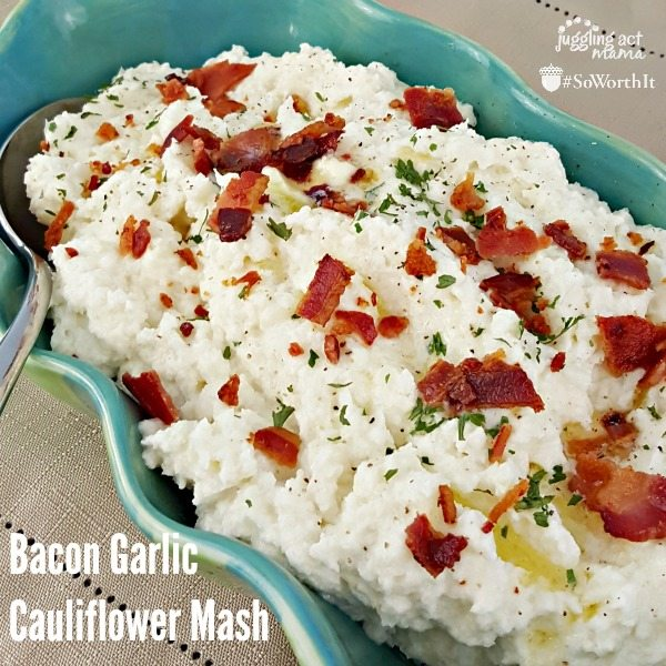 Bacon garlic mashed cauliflower in a blue serving dish, topped with crumbled bacon with a spoon in the dish.