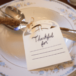 Thanksgiving Gratitude Place Card tied around a spoon and sitting on a plate.