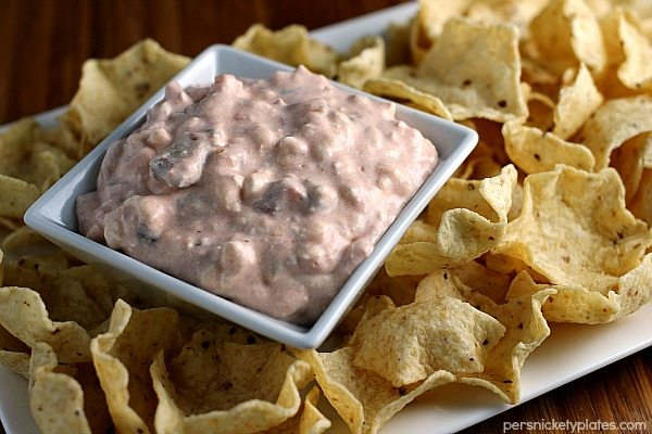 Horizontal image containing cream cheese salsa dip in a square white dish with tortilla chips.