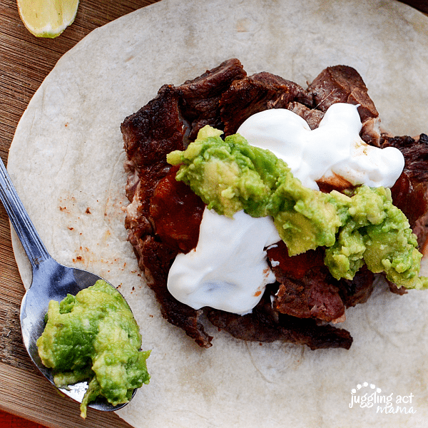 Slices of seared strip steak is piled on top of a tortilla wrap, with sour cream and guacamole topping it off for this Steak Taco Recipe. In the foreground, out of focus, there is a spoonful of guacamole.