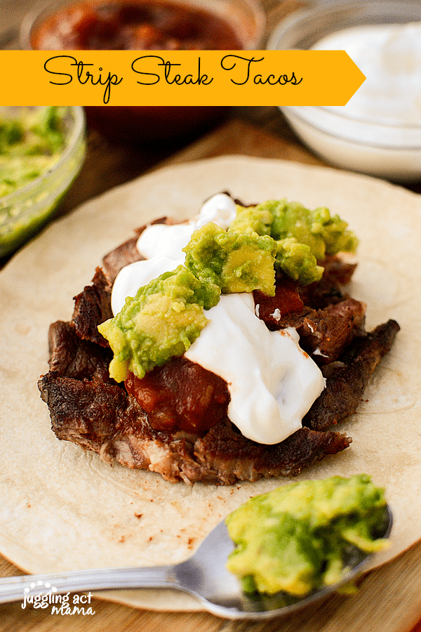 Slices of seared strip steak is piled on top of a tortilla wrap, with sour cream and guacamole topping it off for this Steak Taco Recipe. Bowls of salsa, sour cream and guacamole can be seen in the background. In the foreground, out of focus, there is a spoonful of guacamole.