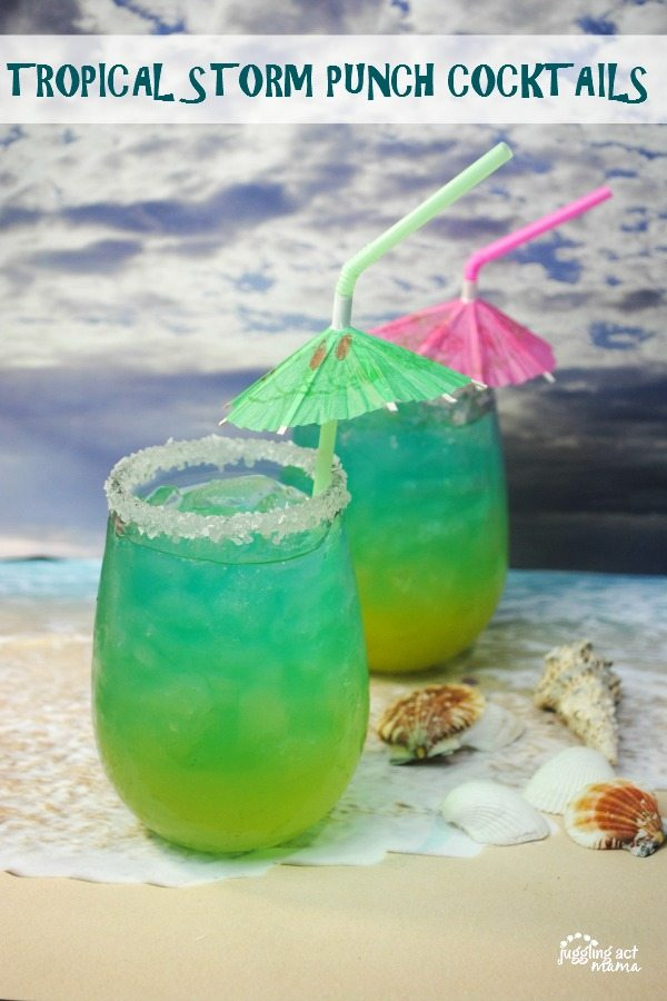 Two green and blue rum cocktails with umbrella straws sit next to seashells as a wave comes in around the bottom of the glasses. A stormy ocean scene is in the background.