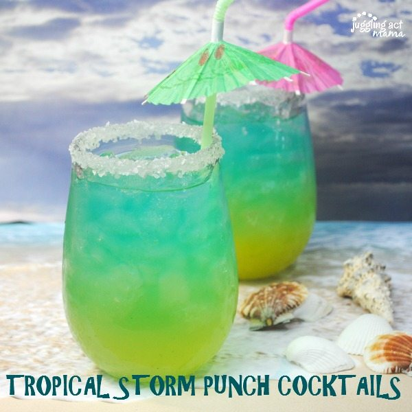 Two green and blue rum cocktails with umbrella straws sit next to seashells in the forefront. A stormy ocean scene is in the background.