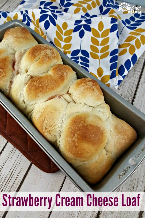 Pull Apart Strawberry Cream Cheese Bread in a 9x5 loaf pan on top of a wooden table with a blue and gold hand towel.