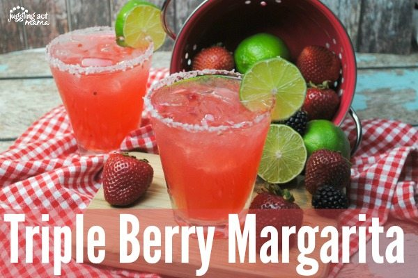 Two berry margaritas with fresh berries spilled around them.