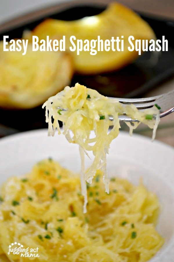 A forkful of baked spaghetti squash recipe garnished with Parmesan cheese and chives. In the back ground is a white pasta bowl full of spaghetti squash and a sheet pan with baked spaghetti squash halves.