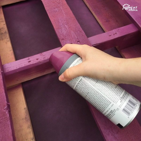 pallet planter being spray painted with purple spray paint.