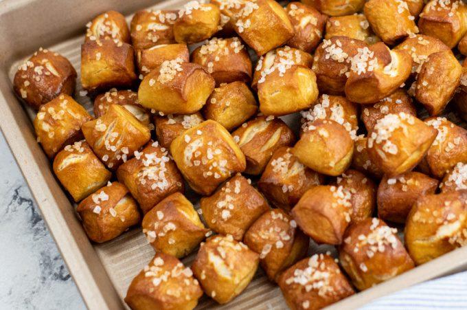 Horizontal image of pretzel bites topped with salt on a sheet pan.