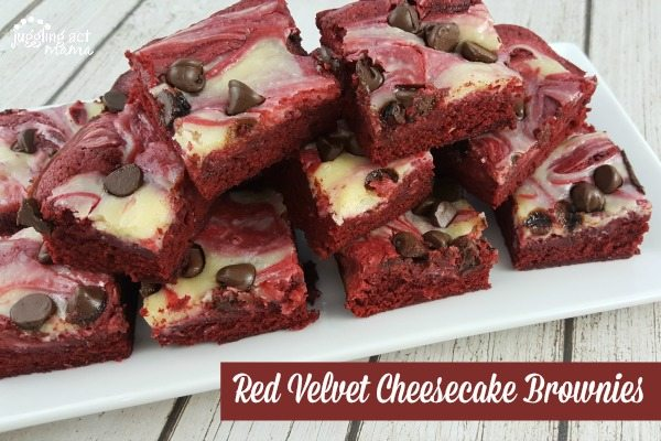 Red velvet cheesecake brownies with chocolate chips stacked high on a white plate on a white wood table.
