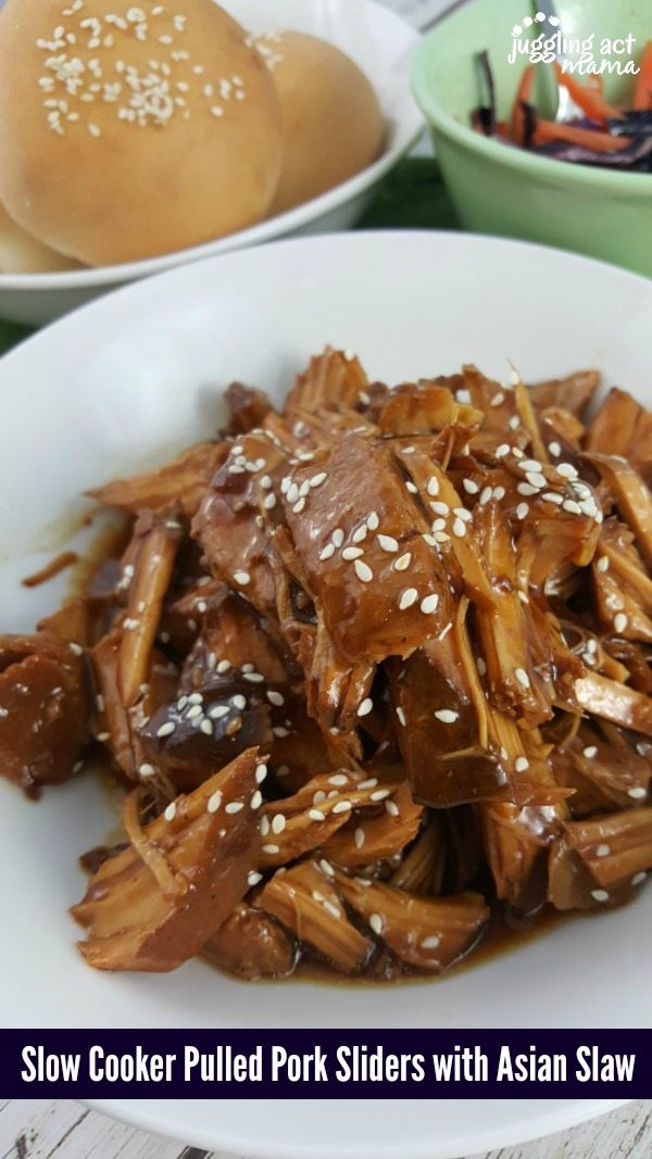 close up of Asian Pulled Pork in a white dish garnished with sesame seeds.