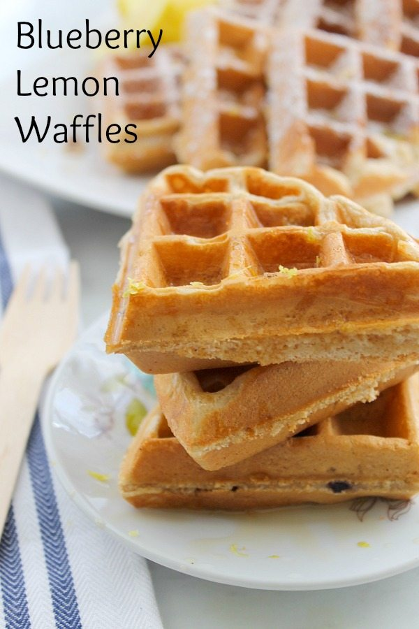 Blueberry Lemon Waffles stacked 3 on a white plate sitting on a white and blue striped napkin.