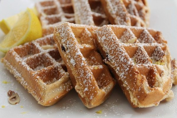 blueberry lemon waffles stacked on each other with a lemon wedge and covered in powdered sugar lying on a white plate.