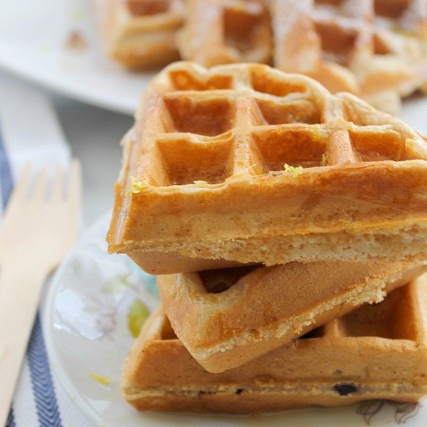 three blueberry lemon waffles stacked on a white plate with delicate flowers. The plate is sitting on a blue and white striped napkin.