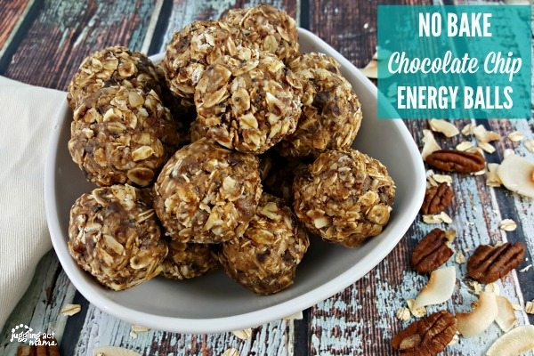 A while bowl filles with Chocolate Chip No Bake Energy Balls sitting on a wooden surface. Pecans and toasted coconut is sprinkled around.