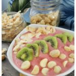 Troptical Strawberry Pineapple Smoothie Bowl with toasted coconut, macademia nuts, and kiwi slices #CleanEating