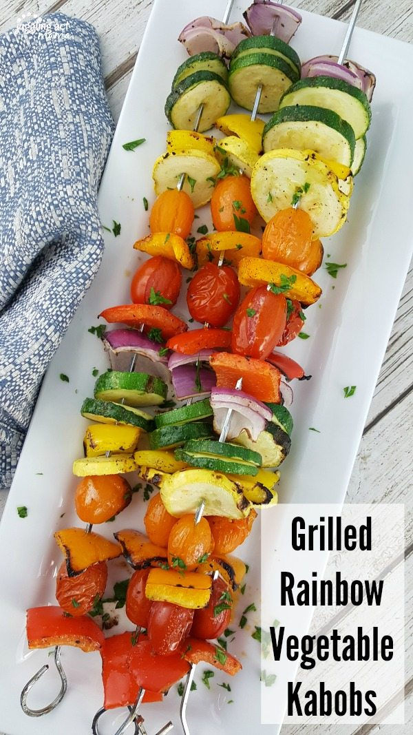 Grilled Vegetable Kabobs with tomatoes, zucchini, summer squash, red onions, plus red, orange, and yellow peppers on metal skewers piled high on a white serving tray next to a blue towel.