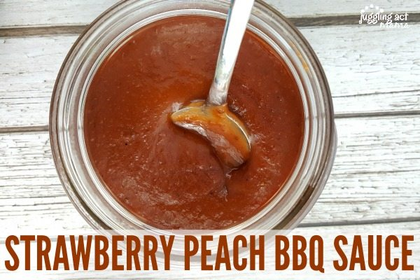 A inside a mason jar of Strawberry Peach BBQ Sauce sits on a white wooden surface.