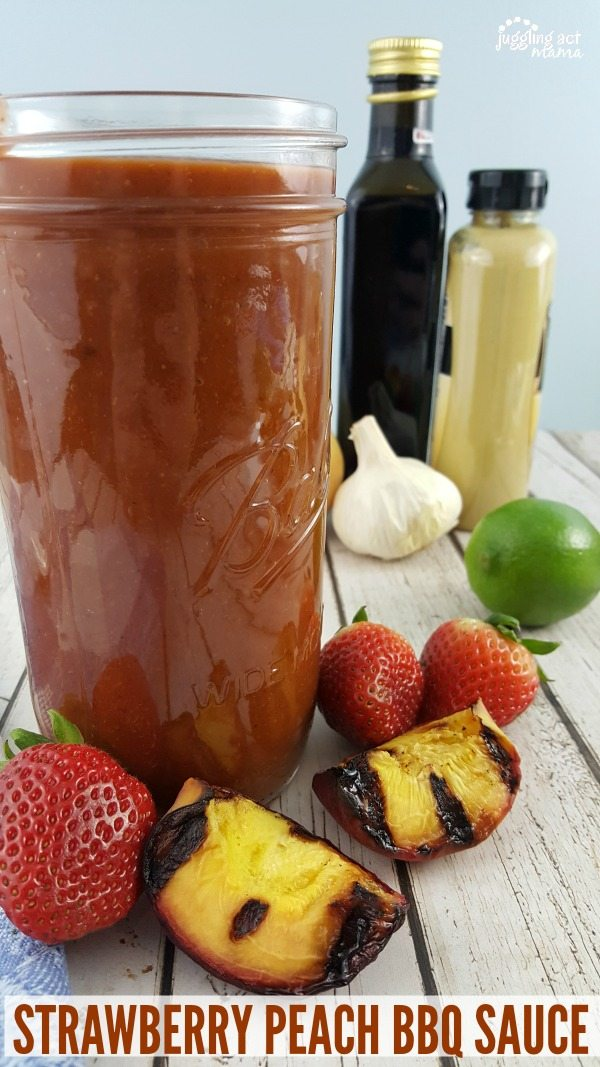 A very full jar of Strawberry Peach BBQ Sauce surrounded by ingredients, including a head of garlic, a whole lime, strawberries and grilled peaches. In the background are bottles of mustard and balsamic vinegar.