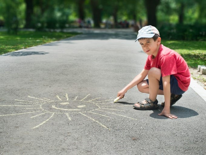 Child drawing sun on asphalt in a park