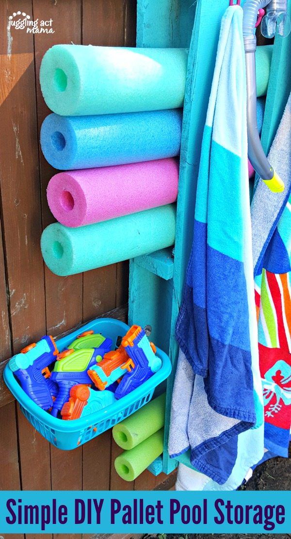 Close up of one of the baskets attached to the wood pallet pool toy holder on the fence. 4 pool noddles are also in view.
