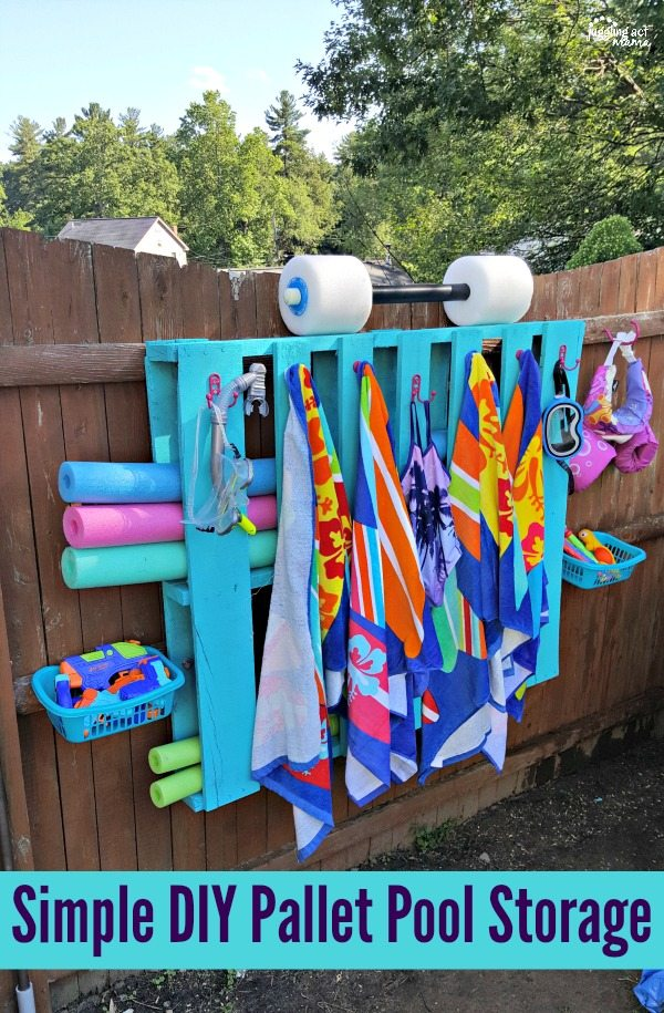 Blue wood pallet functioning as pool storage with blue, pink and green pool noodles, goggles, a snorkel, 6 hooks with colorful towels, 2 baskets on either side holding pool toys and a puddle jumper life jacket.