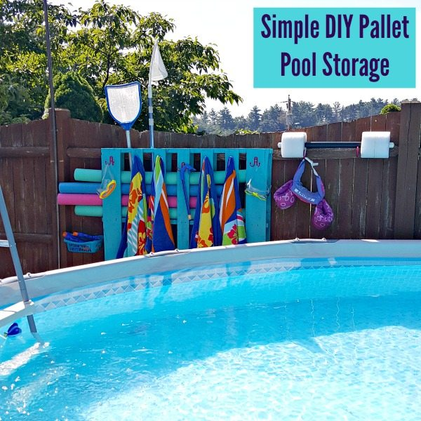 Pool in the foreground - in the background, Blue wood pallet hung on a brown fence. The wood pallet is holding 6 different colored pool noodles, 4 colorful towels, snorkels and goggles, 2 floats, a pool skimmer and has 2 blue baskets attached which are holding various pool toys.