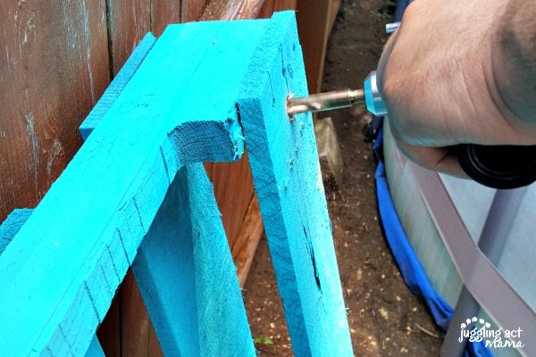 Male hand using a drill to screw together a blue wood pallet.