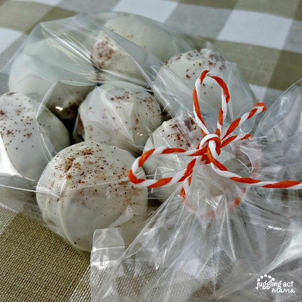 Pumpkin Cream Cheese Cake Balls covered in white chocolate and sprinkled with cinnamon are in a clear celephane bag tied with orange and white baker's twine sitting on top of a tan and white checkered cloth.