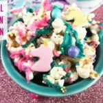 Magical Unicorn Popcorn covered with sprinkles and melted chocolate in blue dish.