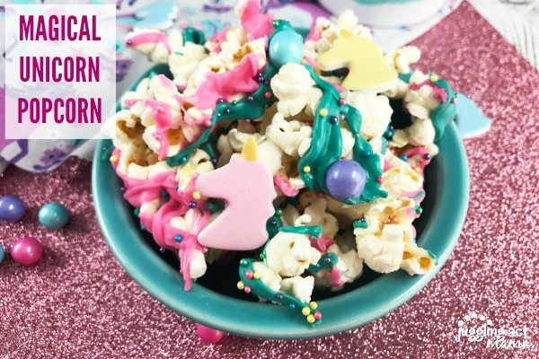 Magical Unicorn Popcorn for Parties - Popcorn with colored chocolate, unicorn shapes, sixlet candies and sprinkles in a teal bowl on top of a glittery pink surface.