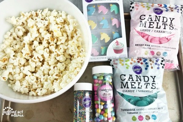 Ingredients for Magical Unicorn Popcorn shown on a baking sheet including a bowl of air popped pocorn, candy melts, sixlets, unicorn candies and sprinkles.