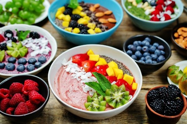 image of various smoothie bowls with smaller bowls of berries, nuts and other ingredients.