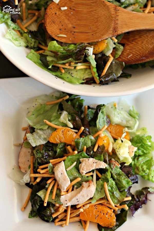 A large white bowl filled with Mandarin Orange Salad at the top of the image, with a white plate piled with the salad including Chow Mein noodles, slivered almonds, and chicken on romaine and red leaf lettuce topped with a poppyseed dressing.